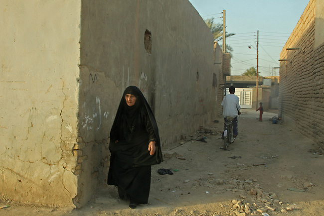 U.S. troops on patrol in Humvees pass an old woman walking out of an alleyway in Samarra, Iraq. Soldiers with Company C, 2nd Battalion, 327th Infantry Regiment encounter hostile fire and IEDs almost daily in the city, but these photos were taken during a rare four-day period when no attacks occurred. Nov. 14, 2007. DREW BROWN/STARS AND STRIPES