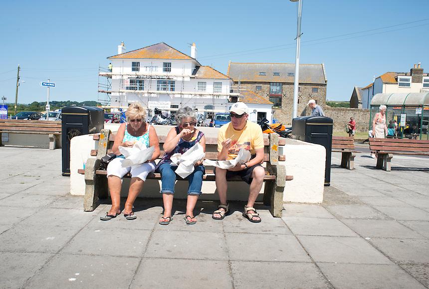 Eating lunch on a Summer day at West Bay, Brid Port, Dorset, UK.