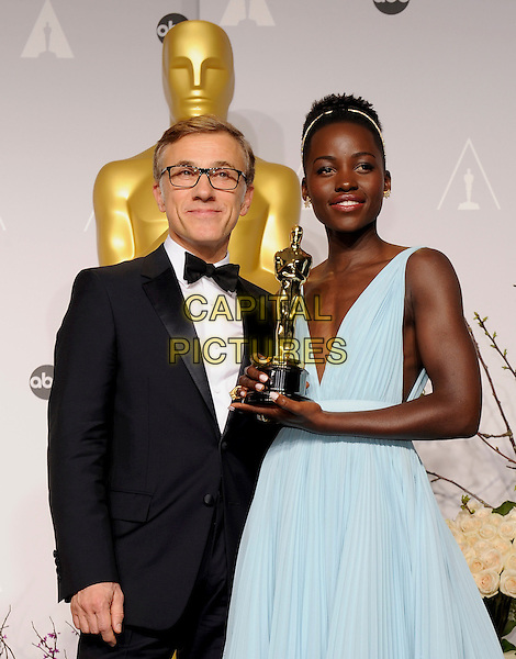HOLLYWOOD, CA - MARCH 2: Christoph Waltz, Lupita Nyong'o in the press room at the 2014 Oscars at the Hollywood and Highland Center in Hollywood, California. March 2, 2014. <br /> CAP/MPI/COR99<br /> &copy;COR99/MediaPunch/Capital Pictures