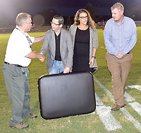 Westside Eagle Observer/MIKE ECKELS<br /> <br /> Toby Conrad (left), Decatur Athletic Director, accepts one of two portable treatment/sideline tables from Brad and Ladale Clayton as Steve Watkins, Decatur superintendent, during half time of the Decatur-Watt, Okla. eight-man football contest at Bulldog Stadium in Decatur Aug. 30.