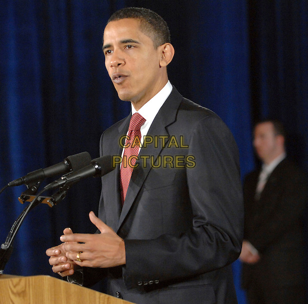 BARACK OBAMA.The Senator makes a speech on the war in Iraq as he makes a campaign stop at the Fayetteville Community College, Fayetteville, North Carolina , USA, .19 March 2008..politics American presidential campaign half  length speaking red tie suit jacket hand wedding ring finger.CAP/ADM/MOO.©Moose/Admedia/Capital Pictures