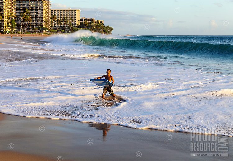 A boy skimboarding with a boogie board is awed by waves at Ka'anapali Beach, Maui.