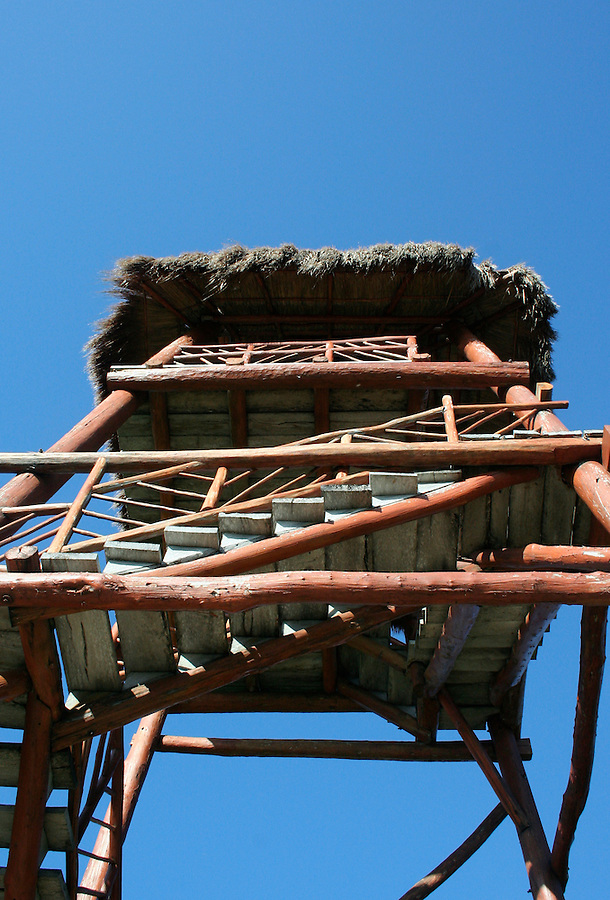 Thatched roof tower with stairs against blue sky
