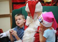 STAFF PHOTO ANDY SHUPE - Joshua Phillips, 7, of Springdale, left, pauses to think of what he wants for Christmas as Santa Claus and Joshua's 5-year-old sister, Cyan, listens while visiting Santa Claus Monday, Dec. 22, 2014, in the Northwest Arkansas Mall in Fayetteville.
