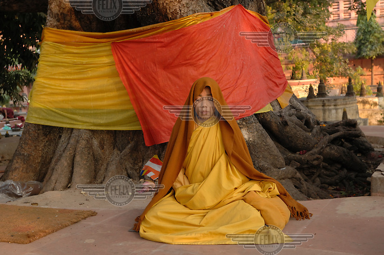 A Buddhist nun meditates at Bodh Gaya, or Bodhgaya, a city famous for being the place of Buddha's attainment of Enlightenment. Thousands of Buddhists from all over the world gather in front of the tree where he reached Nirvana. For Buddhists, Bodh Gaya is the most important of the main four pilgrimage sites related to the life of Gautama Buddha. Since 1953, Bodh Gaya has been developed as an international place of pilgrimage. Buddhists from all over Asia have established monasteries and temples within easy walking distance of the Mahabodhi compound.
