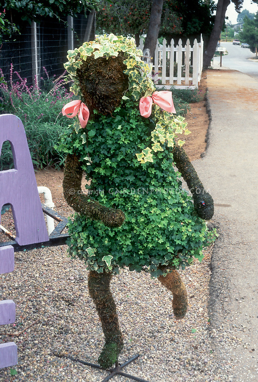 "Topiary of little girl child skipping, ""blonde"" hair, Hedera ivy, pink bows, cute and funny, children's garden appal, next to sidewalk"