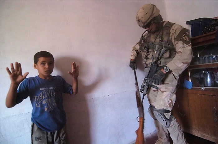 An Iraqi boy surrenders the family shotgun to a U.S. soldier in Rawah, Iraq. The gun was returned to the family for their personal protection. Sunday July 24, 2005.