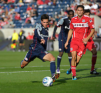 New England midfielder Benny Feilhaber (22) shoots the ball in front of Chicago defender Josip Mikulic (23).  The Chicago Fire defeated the New England Revolution 3-2 at Toyota Park in Bridgeview, IL on Sept. 25, 2011.