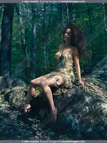 Beautiful sexy half naked young woman sitting on a rock in a forest with closed eyes in a seductive sensual pose wearing a light summer dress revealing her naked breasts and a garter on her thigh