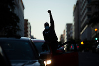 A man raises his fist from his vehicle to express support for protestors in Washington, D.C., U.S., on Sunday, May 31, 2020, following the death of an unarmed black man at the hands of Minnesota police on May 25, 2020.  Credit: Stefani Reynolds / CNP/AdMedia