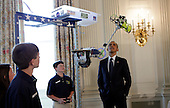 """United States resident Barack Obama  looks at the Robot """"Vator"""" created and presented by Victoria Flechter, Rush Lyons, and Thomas Shields from St Vincent de Paul, Theodore Alabama in the State Dining Room of the White House in Washington, D.C. during the White House Science Fair on April 22, 2013. It mimic space space elevators by carrying cargo up a 10 foot pole.The White House Science Fair celebrates the student winners of a broad range of science, technology, engineering and math (STEM) competitions from across the country. The first White House Science Fair was held in late 2010. <br /> Credit: Aude Guerrucci / Pool via CNP"""