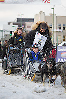 Mike Santos and team leave the ceremonial start line with an Iditarider at 4th Avenue and D street in downtown Anchorage, Alaska during the 2015 Iditarod race. Photo by Jim Kohl/IditarodPhotos.com