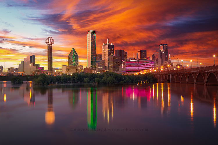 """Dallas Skyline at Dusk"" - Illuminated by a blend of ambient and artificial light, sunset radiates off the Dallas skyline as the city is reflected back in the flooded Trinity River. As the sun prepares to dip below the horizon, Bank of America Plaza (centered) glows neon green while lights on the iconic Reunion Tower (far left) flash and sparkle, bringing the city to life as the night quickly approaches."