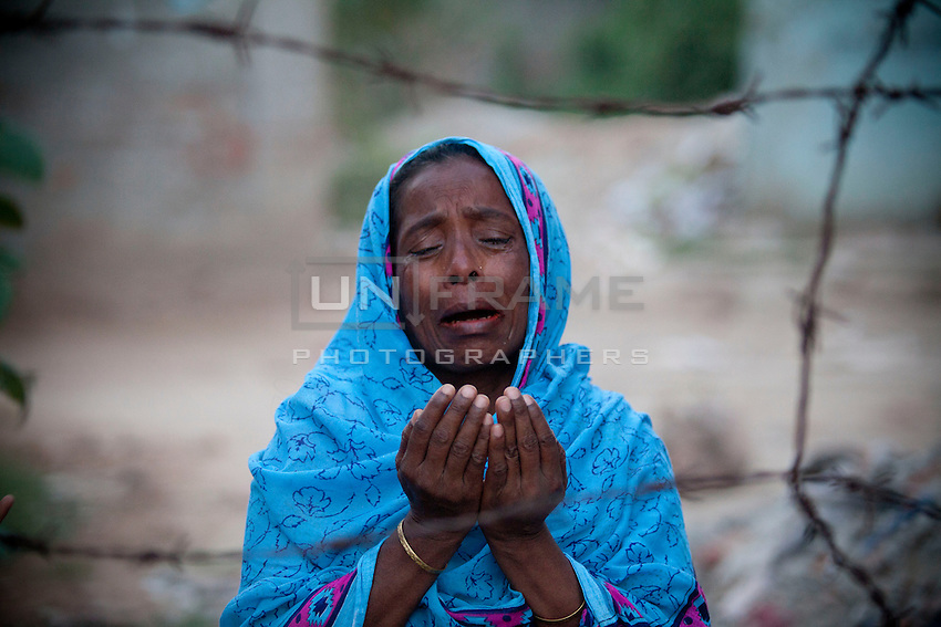 A woman prays and cries for her son, in front of Rana Plaza's ground zero. Relatives of the victims of the April 24 Rana Plaza building collapse gather to pay tributes at the venue of the tragedy at Savar, on the outskirts of Dhaka, Bangladesh, 23rd April 2014.