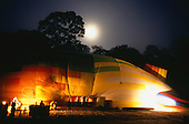 Makande, Gabon. Early morning; the dirigible being prepared for take-off in artificial light with the moon above.