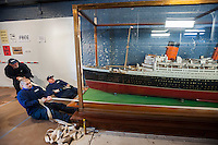 Workers pull the 1/45 th scale model of the Queen Mary to move it from the South Street Seaport Museum in New York on Wednesday, January 21, 2015. The Bassett-Lowke model, originally gracing the Cunard Line ticket offices is being loaned to the Queen Mary itself, now a museum located in Long Beach, CA. The model is carved out of a single mahogany log, over 20 feet long and decorated with hand-carved details. The Queen Mary will dedicate a Model Ship Gallery where the miniature will be the centerpiece. (© Richard B. Levine)