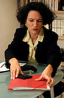 Anxious looking businesswoman looking for documents inside a folder on her desk.