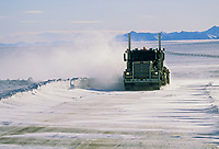 Semi travels the dalton highway during high winds and blowing snow, north of the Brooks Range, on Alaska's Arctic coastal plains.