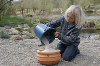 Kinder bauen eine Sonnenuhr, Blumentopf wird mit Sand befüllt