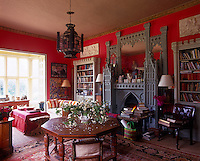 A gothic overmantel complete with mirror is flanked by a pair of castellated bookcases in a bright red living room