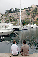 International University of Monaco students Felix (left) and Salvatore (right) spend time on the quayside in the Port of Fontvielle, Fontvielle, Monaco, 19 April 2013. The Prince's Palace of Monaco can be seen at the top of the cliff behind (top right).
