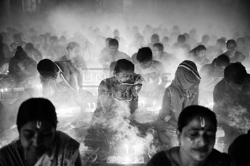 """During Kartik, """"the holiest month"""" beginning every year with the new moon in November, thousands of Hindu devotees celebrate the feast of Rakher Upobash, fasting and praying the gods sitting before the Shri Shri Lokanath Brahmachari Ashram, among the Swami Bagh Temple near Dhaka, Bangladesh. The worshippers offer candles called Prodip, meditate, give to charity, and generally perform austerity. <br /> The faithful pray while thick clouds of incense raise into the air.<br />  Barodi, Dhaka, Bangladesh. Nov. 08, 2014"""