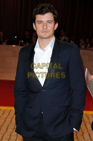 Orlando Bloom.'The Three Musketeers in 3D' world film premiere, Vue cinema, Westfield, London, England. 4th October 2011.half length black suit white top hands in pockets.CAP/CJ.©Chris Joseph/Capital Pictures.