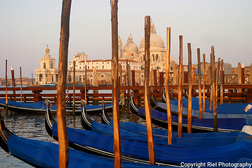 Early morning dawn, the sun rises on the piling poles supporting the sleepy night of the gondolas, Venice, Italy