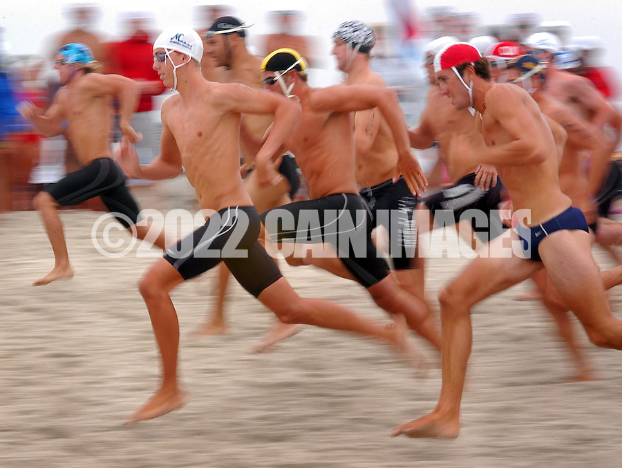 CAPE MAY, NJ - AUGUST 9: Lifeguards run on the beach as they compete in the Run-Swim-Run event during the United States Lifesaving Association Lifeguard Championships August 9, 2003 in Cape May, New Jersey. Lifeguards from all over the U.S. and Canada compete for the title of National Champion not for prizes, but for the right to say they are the best lifeguards in the country. Lifeguards compete in Surf Swim, Rescue Board Races, Surf Boat Races, Ironman/Ironwomen, and Beach Flag events for three days every August. This year the event was held in Cape May, New Jersey. (Photo by William Thomas Cain/Getty Images)