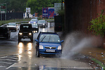 © Joel Goodman - 07973 332324 . 06/09/2013 . Manchester , UK . Cars plough through large puddles in the road . Dark , wet skies above rainsoaked streets of bleak, cloudy Manchester this morning (Friday 6th September 2013) . Rainy weather spells the end of summer in Manchester . Photo credit : Joel Goodman