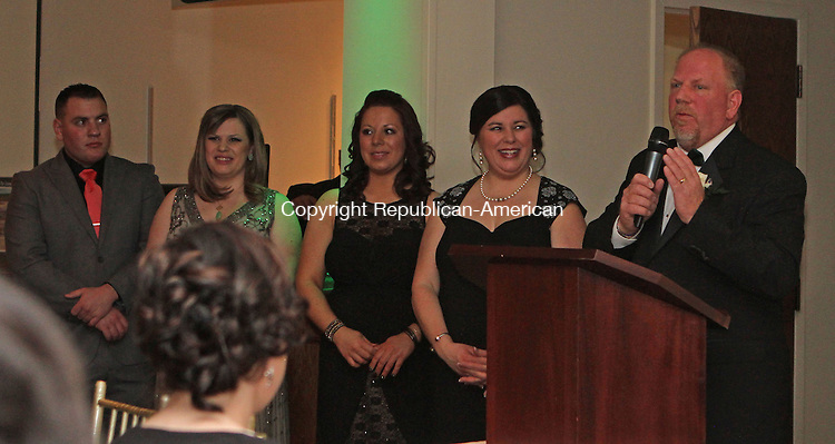 Wolcott, CT-031514MK11 Wolcott's mayor Thomas Dunn delivers remarks as his family (from left: son Thomas, Bridget and Brittany and wife Lisa) react during the annual town celebration at Mahan's Lakeview on Saturday night.  Mayor Dunn was re-elected to become Wolcott's longest serving mayor. Michael Kabelka / Republican-American
