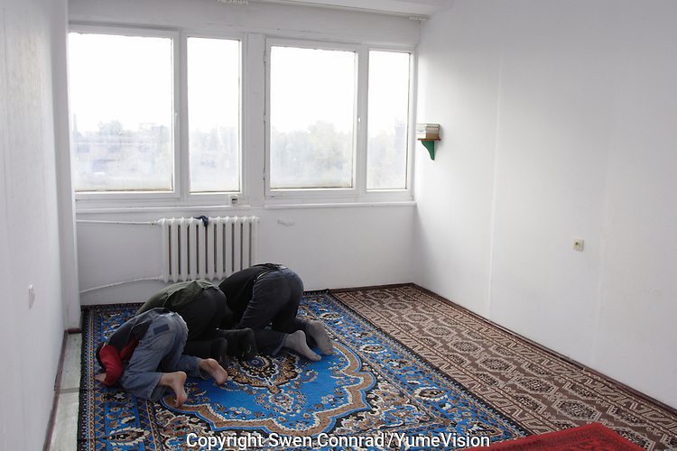 Chechen men and a boy praying while the midday Ramadan pray in the former workers hotel room transformed into a mosque,  in the URiC Bielany Refugee Centre..-For security reason, the face of the adult asylum seeker have been evicted of the photography..-For security reason, the names of the adult asylum seeker have been change. .-Article 9 of the Act of 13 June 2003 on grating protection on the Polish territory (Journal of Laws, No 128, it. 1176) personal data of refugees are an object of particular protection..-Cases where publication of a picture or name of asylum seeker had dramatic consequences for this persons and is family back in Chechnya. .Please have safety of those people in mind. Thank you.