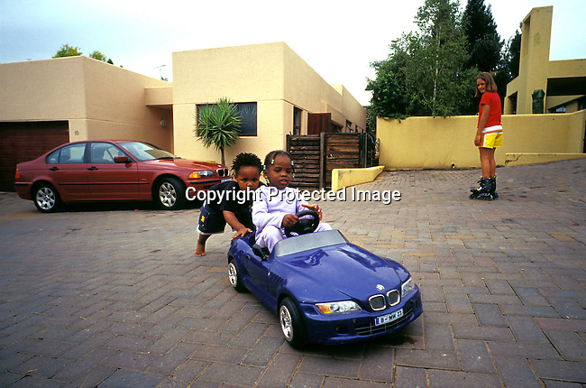 African,Children,Car, White,Girl,Black ,Up-market, JOHANNESBURG, SOUTH AFRICA - FEBRUARY 15: Lebone Dube (right), age 4, with her friend playing with a model BMW car in the driveway of their house on February 15, 2004 in Cedar Lake, a up-market gated community in Johannesburg, South Africa Her father, Oscar Dube, works as a Key Account manager for the Swedish mobile phone equipment maker Ericsson and his wife, Mpho Dube, is fund manager at Old Mutual, an insurance company in SA. They belong to the new black elite in SA. Lebone attends an exclusive pre-school with mostly white children and she invited them for her birthday party. Well educated and connected, they have risen from the poverty in the townships to a very different lifestyle, since the fall of Apartheid and the start of democracy in the country in 1994. .©Per-Anders Pettersson/iAfrika Photos...