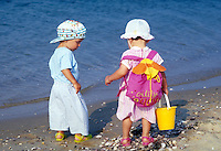Toddler boy and girl in beach clothes at water's edge.
