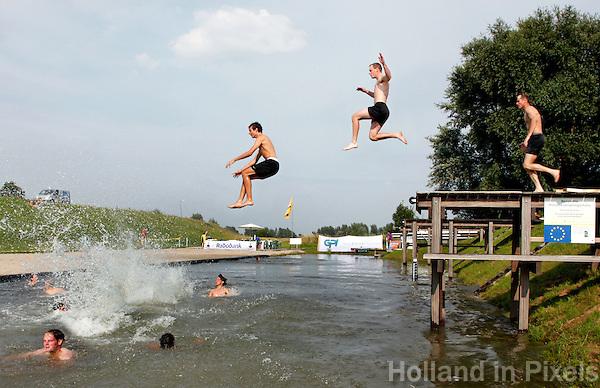 Mensen springen in het water na  een wedstrijd  polsstokspringen