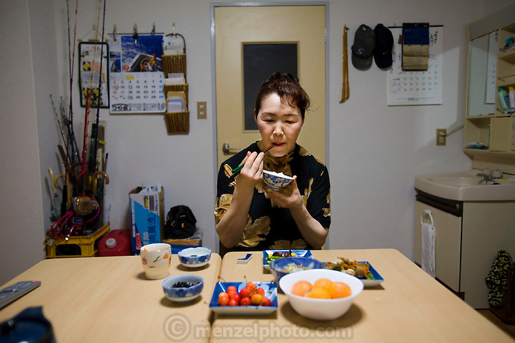 Masako Mizuhashi, a plastic food artist, eats at home during a lunch break in suburban Tokyo, Japan, with her typical day's worth of food (made of plastic) on the table. (From the book What I Eat: Around the World in 80 Diets.)  MODEL RELEASED.