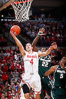 Ohio State Buckeyes guard Aaron Craft (4) puts up a shot under pressure from Michigan State Spartans guard/forward Branden Dawson (22) and Michigan State Spartans forward Adreian Payne (5) in the first half of the NCAA men's basketball game between the Ohio State Buckeyes and the Michigan State Spartans at Value City Arena in Columbus, Ohio, Sunday afternoon, March 9, 2014. As of half time the Michigan State Spartans led the Ohio State Buckeyes 38 - 36. (The Columbus Dispatch / Eamon Queeney)