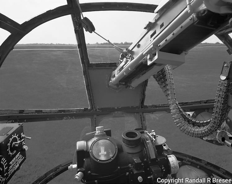 &quot;Bombardier's View in a B-25&quot; <br /> <br /> This black and white photo shows the bombardier's view in a B-25 &quot;Mitchell&quot; bomber. The B-25 began service early in World War II as a medium bomber and soon proved to be effective for strafing because of the number of its forward firing guns. The B-25 became well known when it was used for the famous Doolittle raid into Japan soon after the bombing of Pearl Harbor. The famous Nordon bombsight is at the bottom center and a bomb &quot;train&quot; control box is at the lower left. The bombardier's 50 caliber machine gun enters the photo from the upper right and barrels of two 50 caliber machine guns that were fired by the pilots can be seen at the lower right and bottom right. The airplane was piloted by Greg Vallero and photographed at the 2012 Memorial Day Weekend &quot;Salute to Veterans&quot; airshow in Columbia, Missouri.