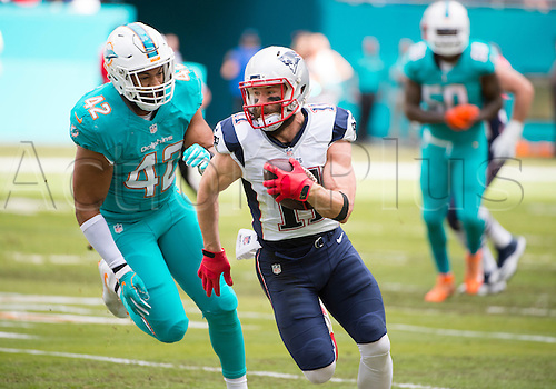 01.01.2017. Miami Gardens, Florida, USA.  New England Patriots Wide Receiver Julian Edelman (11) runs with ball and is pursued by Miami Dolphins Linebacker Spencer Paysinger (42) during the NFL football game between the New England Patriots and the Miami Dolphins on January 1st 2017, at the Hard Rock Stadium in Miami Gardens, FL.