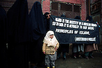 Indian Kashmiri women activists of an Islamic organization Dakhtran-I- millat display a banner during a demonstration at Srinagar against the ban of headscarves by the French Government. Kashmir Valley, India