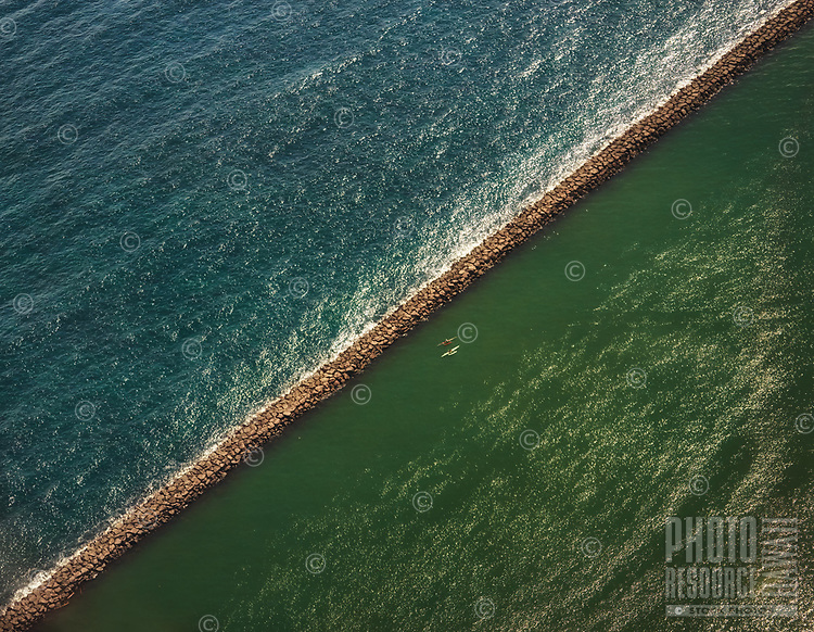 An aerial view of two kayaks at the surf break rock wall of Hilo Bay, Big Island.
