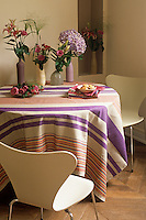 In the dining area roses, lilies and hydrangeas have been arranged in ceramic vases to complement a contemporary striped tablecloth