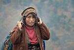 A woman carries a heavy bundle using a head strap in the village of Gatlang, in the Rasuwa District of Nepal near the country's border with Tibet.
