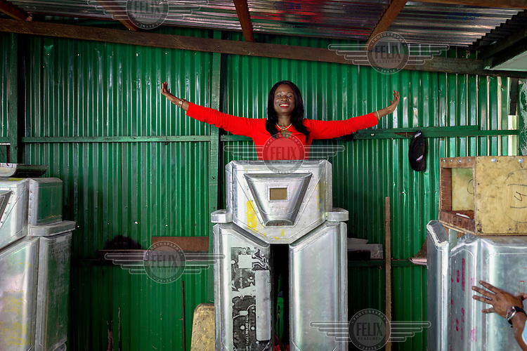 Therese Kirongozi, president of Women's Tech, stands behind an unfinished traffice robot in the workshop behind one of her other enterprises, a restaurant. Women's Tech designs and manufactures humanoid traffic robots which are solar powered, equipped with light signals and cameras and are employed by the city authorities to monitor and control urban traffic.
