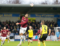 5th January 2020; Pirelli Stadium, Burton Upon Trent, Staffordshire, England; English FA Cup Football, Burton Albion versus Northampton Town; Michael Harding of Northampton Town jumps to head the ball down field over Jake Buxton of Burton Albion  - Strictly Editorial Use Only. No use with unauthorized audio, video, data, fixture lists, club/league logos or 'live' services. Online in-match use limited to 120 images, no video emulation. No use in betting, games or single club/league/player publications