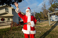 STAFF PHOTO JASON IVESTER --12/12/2014--<br /> Santa, portrayed by Ronnie Flowers of Bentonville, welcomes visitors on Friday, Dec. 12, 2014, outside the Lowell Historical Museum. The museum hosted a Christmas open house to visitors.