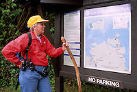 Cape Scott Provincial Park, Northern Vancouver Island, BC, British Columbia, Canada - Hiker reading Map and Sign at Start of Hiking Trail (Model Released)