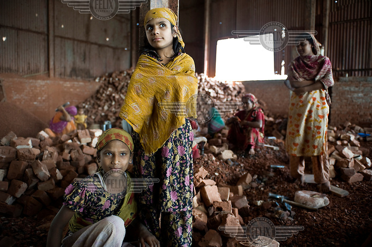 12 year old Tania (left) and 10 year old Sonia work breaking up brick and stone into ballast to be used in concrete. Many children are employed in this work, earning between 25-50 Euro cents a day.