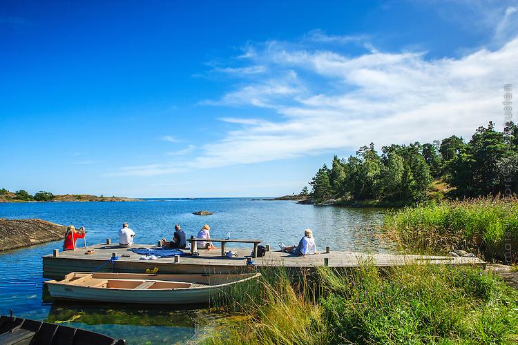 Människor sitter på en brygga vid havet på Utö i Stockholms skärgård