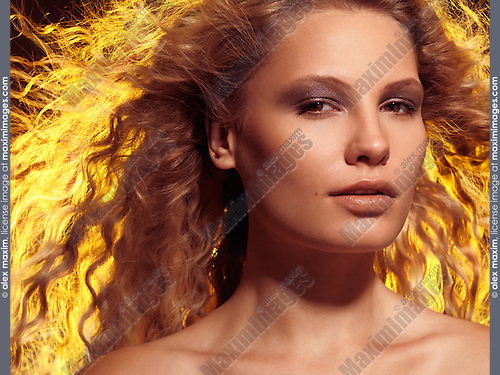 Beauty portrait of a young smiling woman with beautiful brightly lit flying golden hair